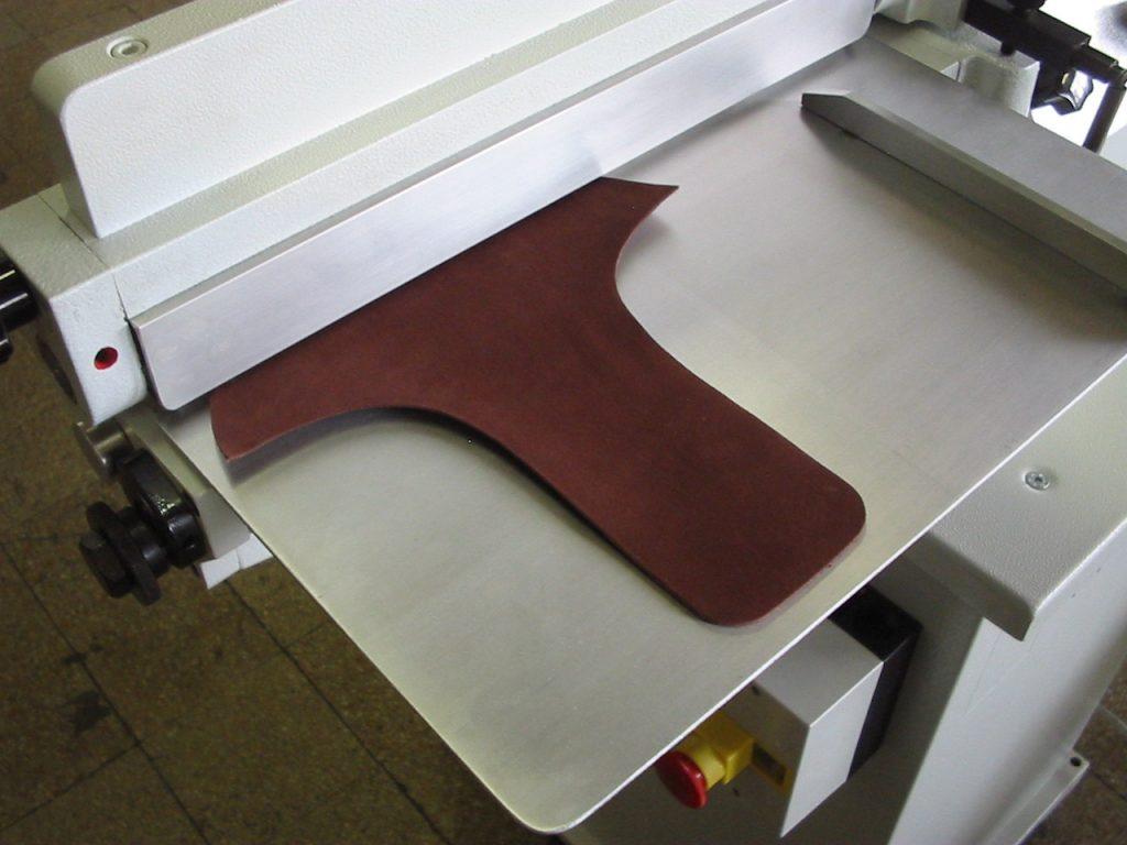 máquina de rodillo aplicando pegamento a plantilla de calzados