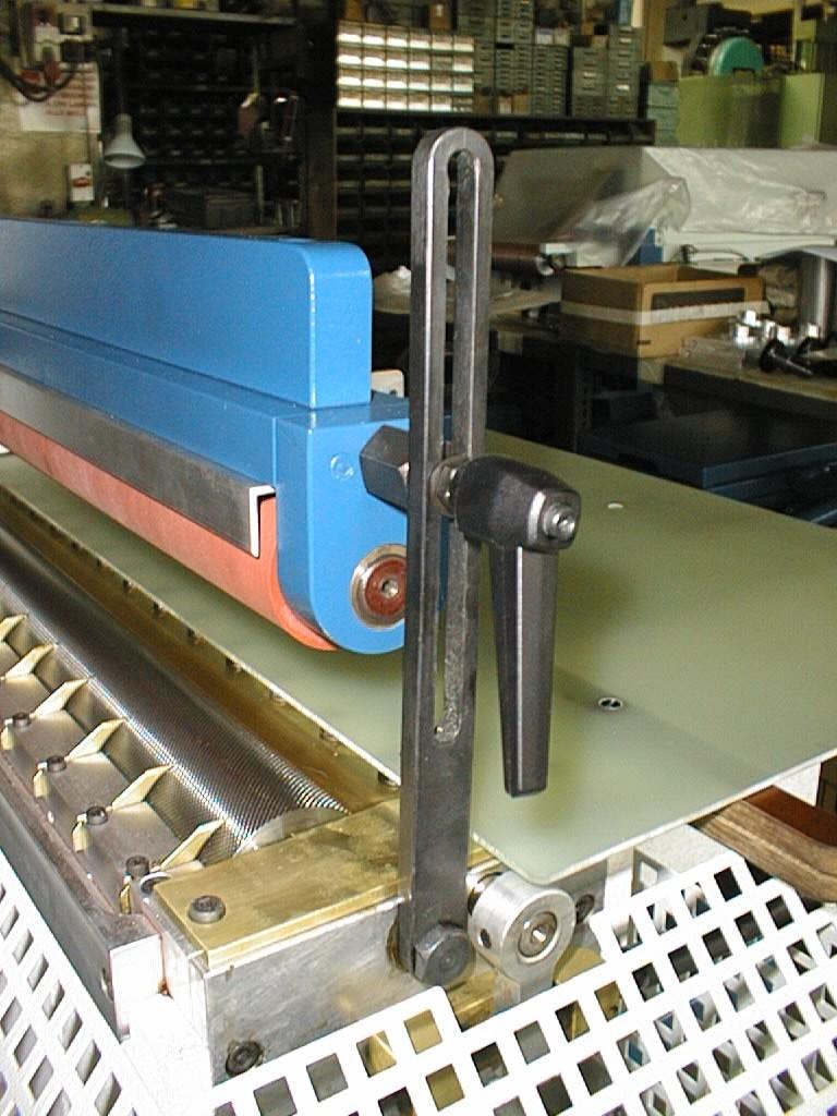mecanismo para graduar la altitud del rodillo central de la máquina